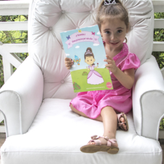 Menina segurando livro infantil personalizado Eu sou uma princesa por um dia